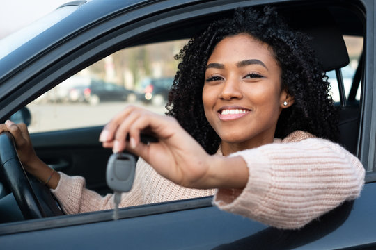 Happy young woman learning to drive car