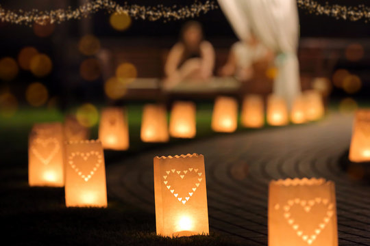 Night party in the garden with empty path lit by lanterns in the shape of hearts