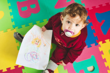 Cute baby girl with dummy on alphabet play mat drawing on paper with a colored crayon