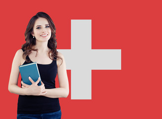 Study, internship and work in Switzerland concept. Beautiful smart woman on swiss flag background