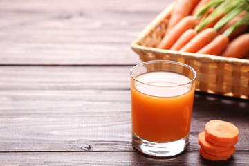 Wall Mural - Fresh carrot with glass of juice on wooden table