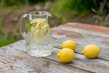 Jar with lemon water and lemons on wooden table, standing outside. Summer time.