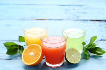 Wall Mural - Citrus juice in glasses with fruits on blue wooden table