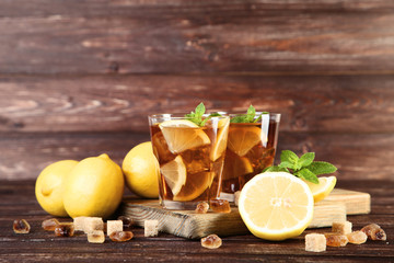 Wall Mural - Ice tea in glasses with lemon and mint leafs on wooden table