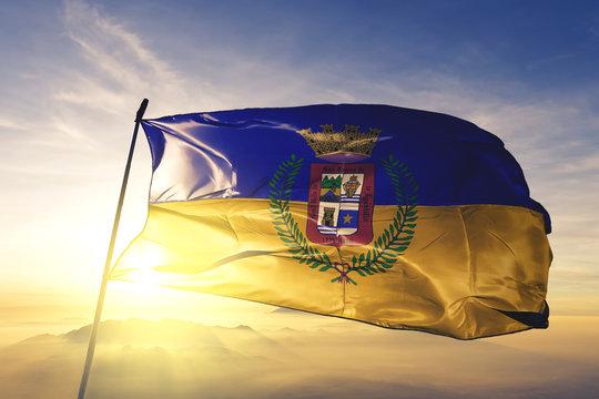 Aguadilla municipality of Puerto Rico flag waving on the top sunrise mist fog