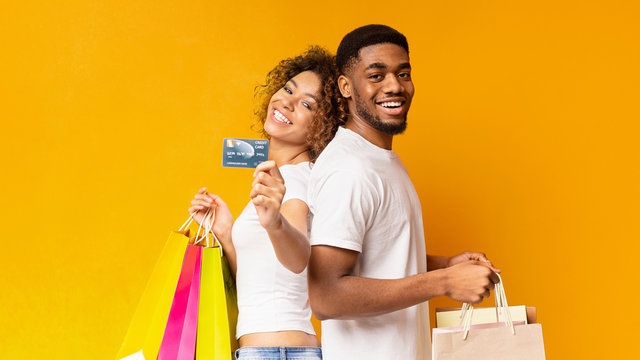 Young black couple with shopping bags and credit card