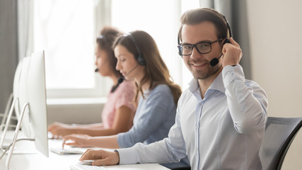 Smiling male call center operator in headset looking at camera Wall mural