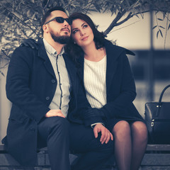 Happy young fashion couple in love sitting on bench