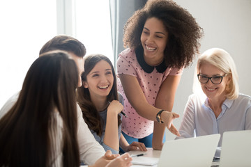 Positive friendly diverse team employees talking laughing at company meeting