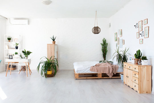 Cozy interior design of modern studio apartment in Scandinavian style. A spacious huge room in light colors with wooden bed and stylish expensive luxury furniture.