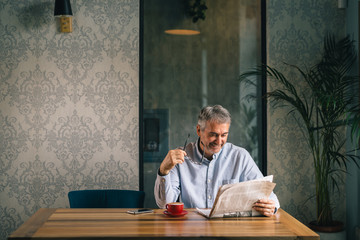 senior man reading newspaper and drinking coffee in cafeteria
