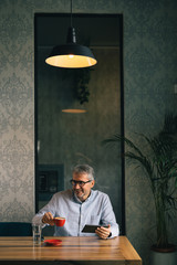 gray haired businessman using tablet and drinking coffee in restaurant