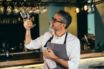 Middle aged barman polishing the wine glass in cafe bar