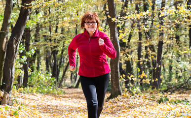 Middle age woman  wearing sportswear and running in forest