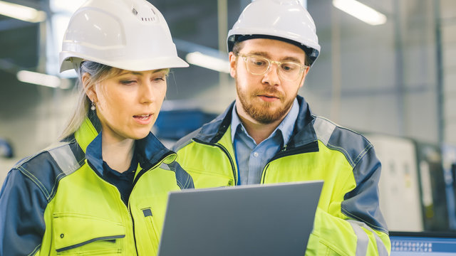 Male and Female Industrial Engineers Work on a Manufacturing Plant, They Discuss Project, Point in the Direction of the Machinery while Using Laptop.