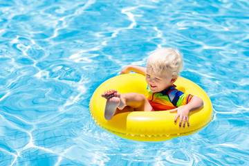 Child in swimming pool on toy ring. Kids swim.