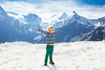 Child hiking in mountains. Kids in snow in spring.