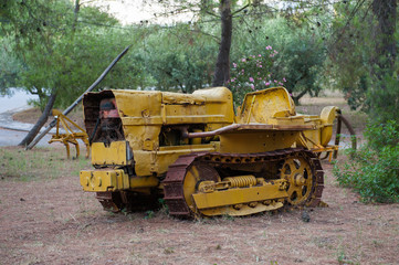 Abandoned bulldozer. yellow mechanical old man. Nature is stronger than technology