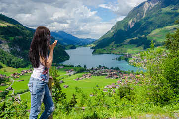 Wall Mural - Girl looks at the panorama of Lungernsee lake near Luzern, Switzerland, Europe