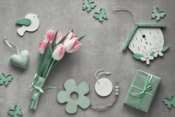 Flat lay on stone surface with pink tulips, wrapped gift box and spring decorations