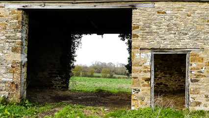 Landscape close up of 18th century stone barn, with open cart doors and views across Oxfordshire countryside. Small doorway, repointing and cracking to walls. Ivy silhouette around far door. Broughton