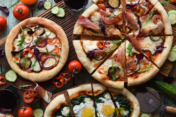 Rustic style pizza party. Homemade puffy pizzas with pancetta, aubergines, spinach, eggs, bell pepper and arugula served with raw ingredients on oak boards