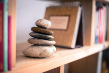 Feng Shui: Stone cairn in a book shelf in the living room, balance and relaxation