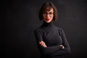 Close-up studio shot of young woman wearing eyewear and red lipstick while standing at dark background