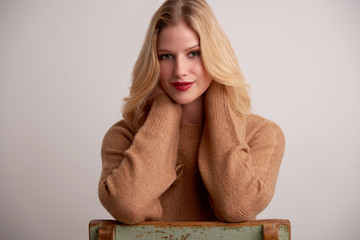 Attractive young woman with blond hair and red lipstick sitting at isolated background