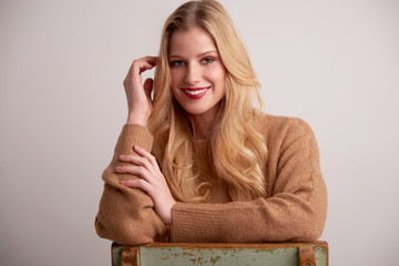 Cheerful young woman with blond hair and red lipstick sitting at isolated background