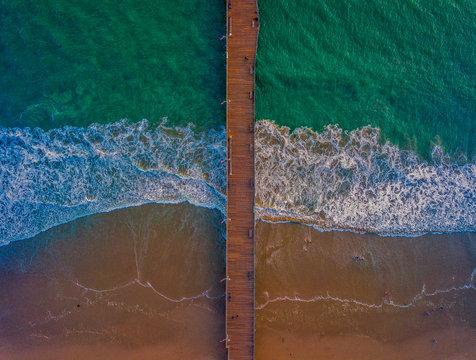 brown wooden dock between sea at daytime
