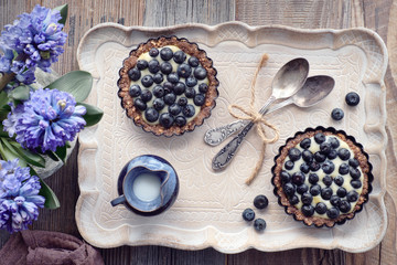 Top view on wholegrain blueberry tarts with vanilla cream on a ceramic tray