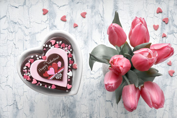 """Valentine heart cake with chocolate, sugar decorations and text """"Happy Valeitine"""" and a bunch of pink tulips"""