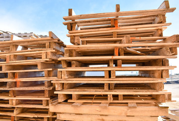 piles of european pallets made in wood ready to be used transporting products or goods on them from a place to other by truck, plane or ship.