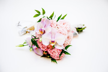 Fresh elegant bouquet of orchids and roach roses, perfume on a white background
