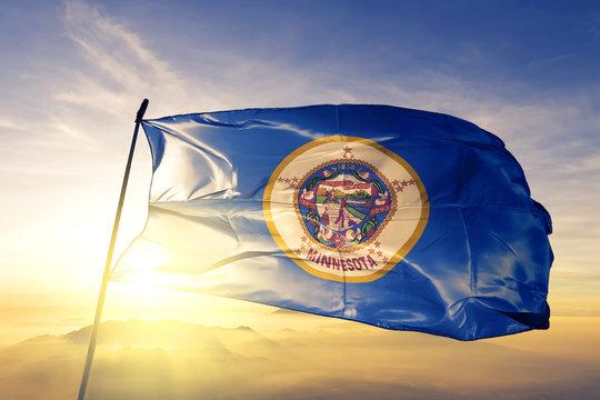 Minnesota state of United States flag waving on the top sunrise mist fog