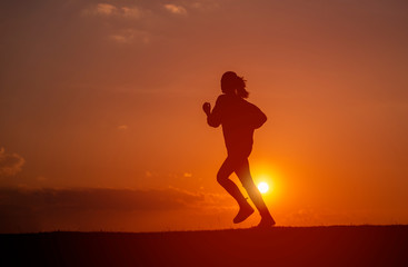 Silhouette of the running girl at sunrise.