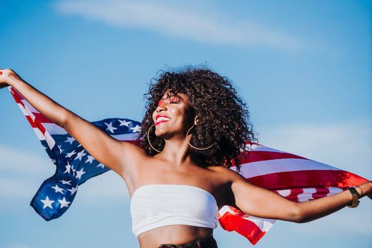 Black woman with afro hair and an american flag celebrating the independence day of USA