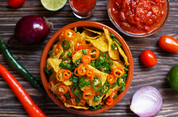 Mexican yellow corn tortilla chips nachos with jalapeno, guacamole, cheese sauce and salsa on a wooden table