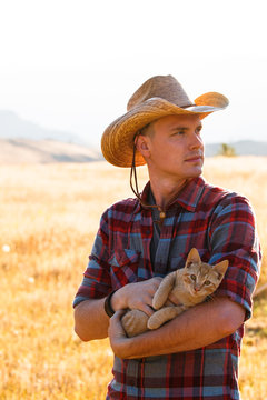 A man with a cowboy hat holds a kitten at sunrise at the Rim Rock Inn in northeast Oregon.