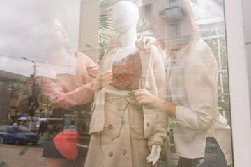 Two girls dress up mannequin at store front window