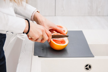 Woman's hands cutting fresh grapefruit on kitchen. Girl cutting orange with knife. Healthy lifestyle concept.