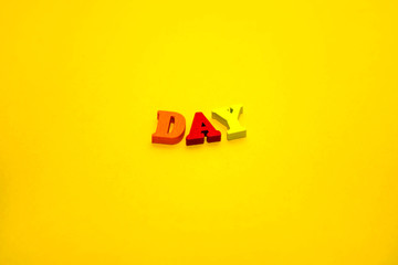 inscription day on the yellow background in wooden multicolored letters. Top view. Flat lay. Copy space for text. minimalism. design concept.