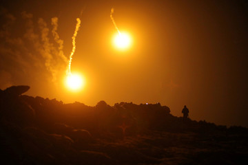 Flares are seen in the sky during fighting in the Islamic State's final enclave, in the village of Baghouz