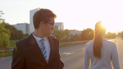 SUN FLARE: Man looking at his phone stops and stares at gorgeous businesswoman