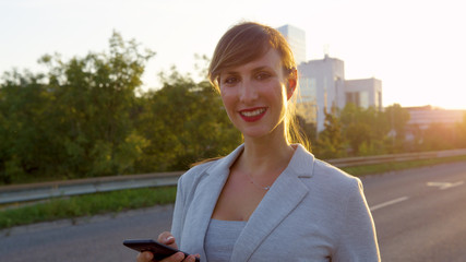 SUN FLARE: Cheerful elegant businesswoman smiles at camera while walking home.