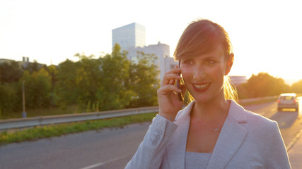 CLOSE UP: Smiling young businesswoman calling her friend after walking home.
