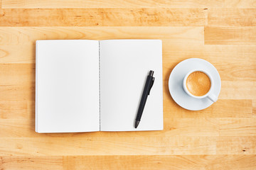Blank notebook, pen and cup of coffee or espresso on yellow wooden table. Office concept. Top view. Copy space for text. Flat lay.