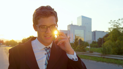 LENS FLARE Golden sunbeams shine on yuppie talking on the phone while going home