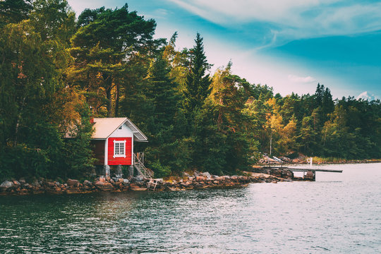 Red Small Finnish Wooden Sauna Log Cabin On Island In Autumn Season